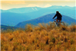Person Riding Bike on Mountains